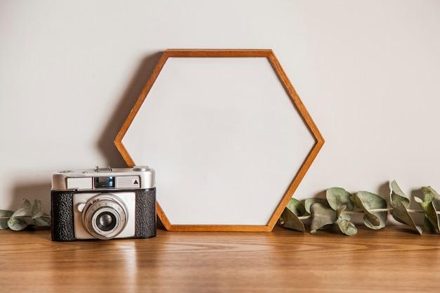 Rama sześciokątna i kamera na powierzchni drewnianych