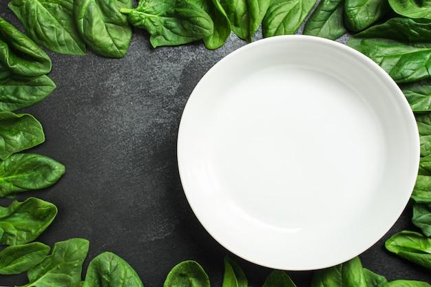 Rama szpinaku i pusty biały talerz. tło żywności. kopia przestrzeń. widok z góry