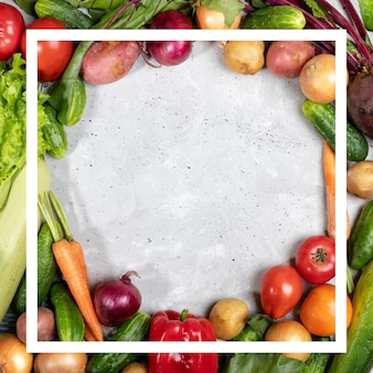 Rama warzywami i kreatywny biały kwadrat ramki na nich na betonowym tle z miejsca kopiowania.