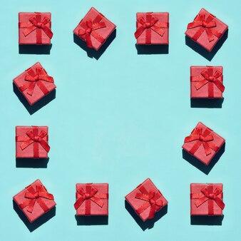 Rama wiele małych czerwonych różowych pudełek prezentowych na zielono