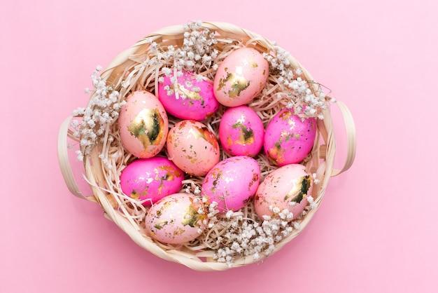 Rama wielkanocne złote zdobione jajka na pastelowym różowym tle.