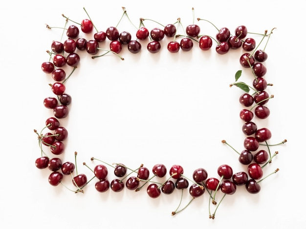 Rama wielkie dojrzałe czereśniowe jagody na białym tle. naturalne lato jedzenie tła. kreatywny układ żywności latem. widok z góry. skopiuj miejsce
