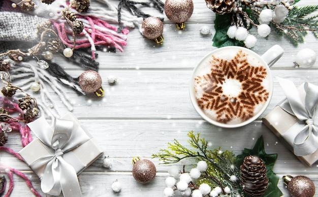 Rama wykonana z dekoracji i kawy z płatkiem śniegu na białej drewnianej powierzchni