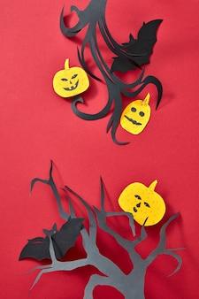 Rama wykonana z gałęzi papieru rzemieślniczego drzew, dyni i nietoperzy na czerwonym tle z miejscem na tekst. karta halloween. płaskie ułożenie