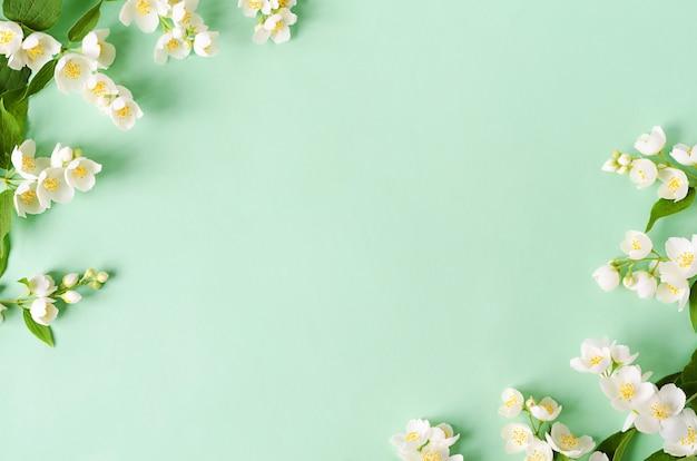 Rama wykonana z kwiatów i gałęzi jaśminu na zielono.