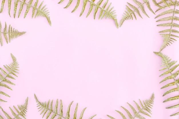 Rama wykonana z liści paproci złote liście na jasnym tle.