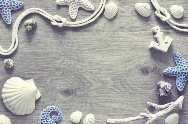 Rama wykonana z muszli morskich, kamieni, liny i rozgwiazdy na jasnej fakturze, copyspace