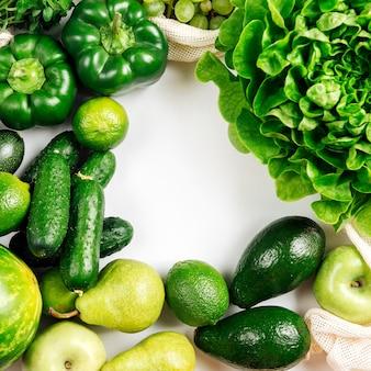 Rama wykonana z organicznych warzyw i świeżych zieleni na białym tle na białym tle