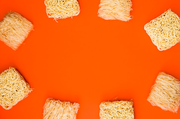 Rama wykonana z różnych bloków surowego makaronu na pomarańczowym tle
