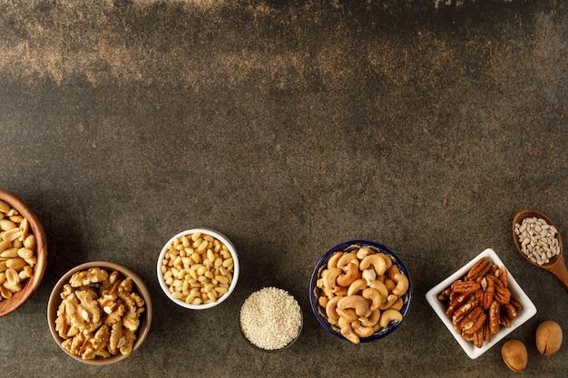 Rama wykonana z różnych rodzajów orzechów w miskach. widok z góry. skopiuj miejsce