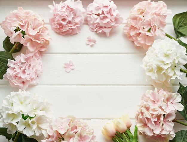 Rama wykonana z różowych i beżowych kwiatów hortensji oraz żółtych tulipanów