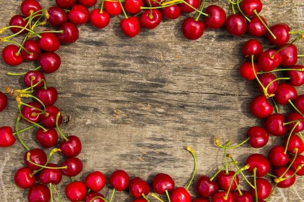 Rama z czerwonej wiśni na drewnianym tle. widok z góry z miejscem na kopię