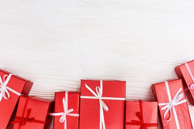 Rama z czerwonych prezentów na białym drewnie