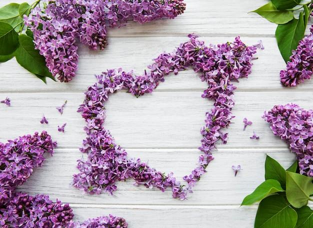 Rama z gałęzi i kwiatów bzu na stole w kształcie serca