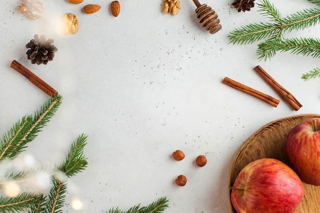 Rama z gałęzi świerkowych, cynamonu, jabłek i orzechów. kartka świąteczna. nowy rok..