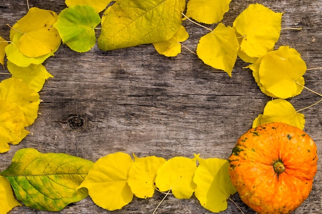 Rama z jesiennych żółtych liści i dyni na rustykalne drewniane tła. widok z góry, kopia miejsca