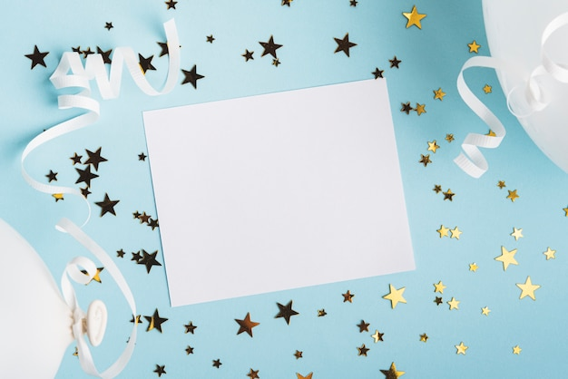 Rama z konfetti gwiazd i balonów na niebieskim tle