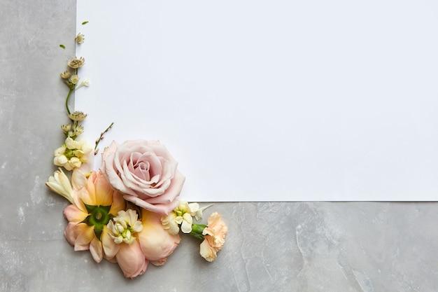 Rama z kwiatami z miejscem na tekst na kamiennym szarym tle, płaskie lay