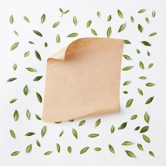 Rama z liści i stary kawałek papieru rzemieślniczego na białym tle z kopią miejsca