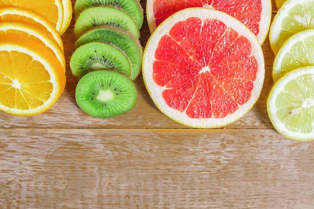 Rama z plasterkiem pomarańczy, cytryn, kiwi, wzór grejpfruta na drewnianym
