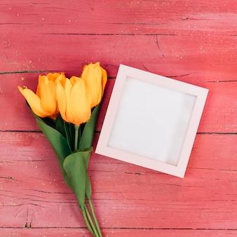 Rama z pomarańczowymi tulipanami na różowym drewnianym tle