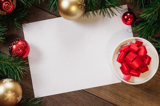 Rama z sosnowych gałęzi i ozdób choinkowych oraz arkusz białego papieru a4 na drewnianym stole. święta bożego narodzenia. copyspace. widok z góry.