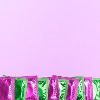 Rama z widokiem z góry z zielonymi i różowymi prezerwatywami