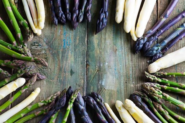 Rama ze świeżo wychowanych naturalnych organicznych szparagów na drewnianym tle.