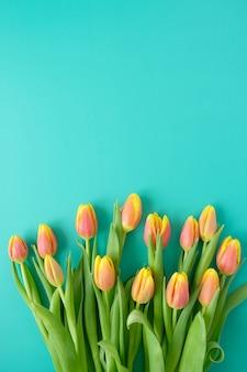 Rama ze świeżych żółto-czerwonych tulipanów na tle mięty. koncepcja międzynarodowego dnia kobiet, dnia matki, wielkanocy