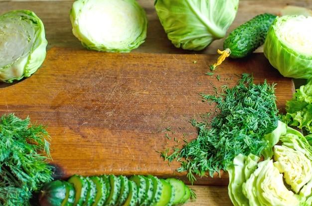 Rama zieleni warzywa i ziele na naturalnym drewnianym tle