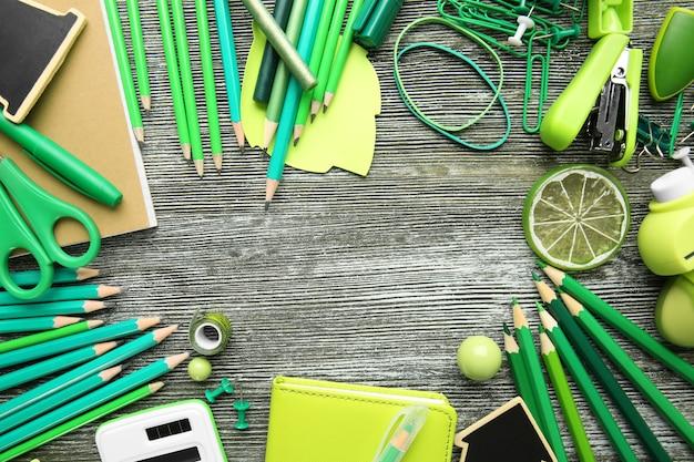 Rama zielonych materiałów biurowych na szarej powierzchni drewnianych