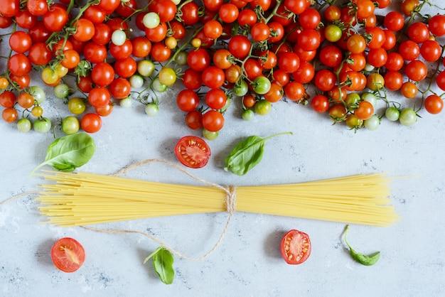 Rama żywności. koncepcja składników makaronu. niegotowane spaghetti i pomidor cherry z zieloną bazylią na niebieskim tle. widok z góry z miejsca kopiowania. włoskie jedzenie
