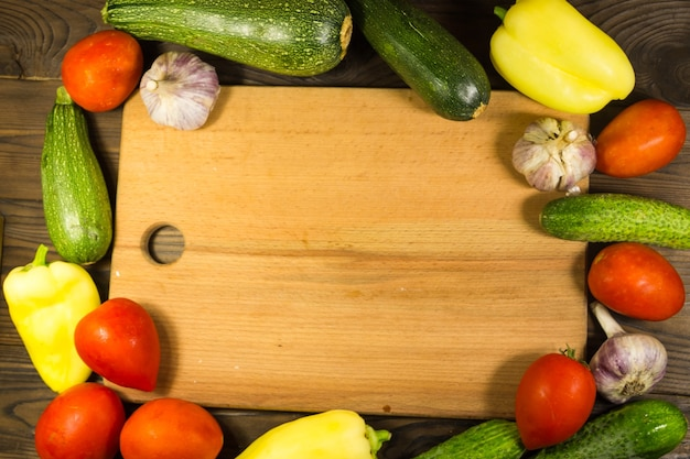 Rama żywności ze świeżych organicznych warzyw. pomidory, ogórki, papryka, cukinia i czosnek na drewnianym stole w kuchni. koncepcja zdrowej żywności