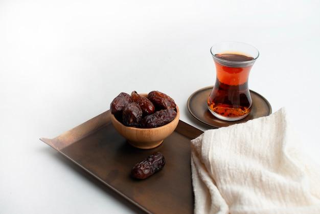 Ramadan kareem festival, daty na drewnianej misce z filiżanką czarnej herbaty i różaniec