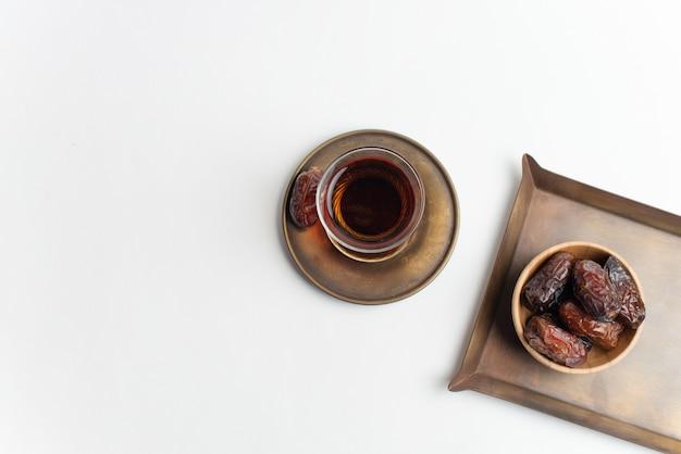 Ramadan kareem festival, daty w drewniane miski z filiżanką czarnej herbaty na białym tle