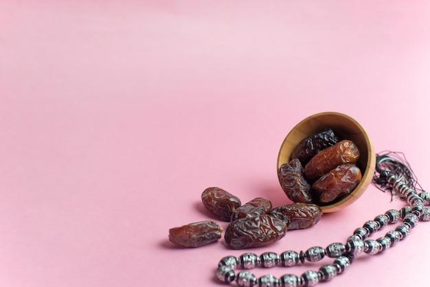 Ramadan kareem festival, daty w misce z różańcem na różowym tle