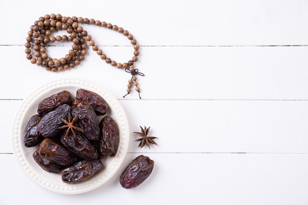 Ramadan koncepcja żywności i napojów. drewniany różaniec i daty owocowi na białym drewnianym stole