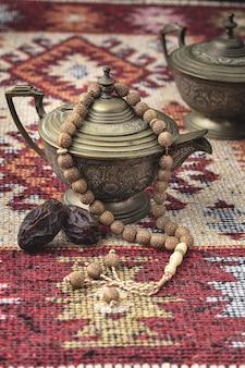 Ramadanowa kompozycja z filiżanką herbaty, koralikami i suszonymi daktylami
