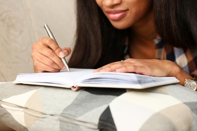 Ramię czarnej kobiety pisze historię w zeszycie