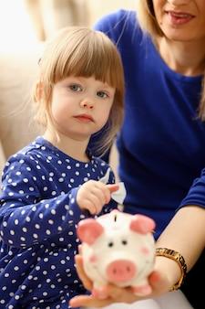 Ramię dziewczynki wkładanie monet do skarbonki