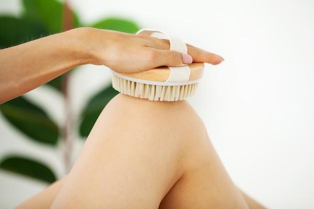 Ramię kobiety trzyma suchą szczoteczkę na szczycie nogi, leczenie cellulitu i szczotkowanie na sucho.