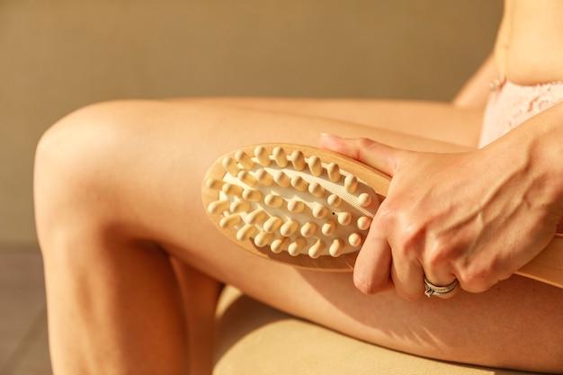 Ramię kobiety trzyma suchą szczotkę do górnej części nogi. piękna młoda kobieta z antycellulitowym pędzlem do masażu.