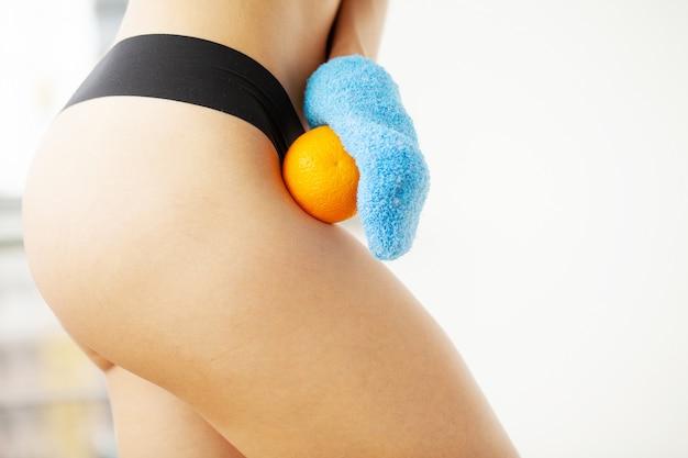 Ramię kobiety trzyma suchą szczotkę na szczycie nogi i pomarańczę, leczenie cellulitu i szczotkowanie na sucho.