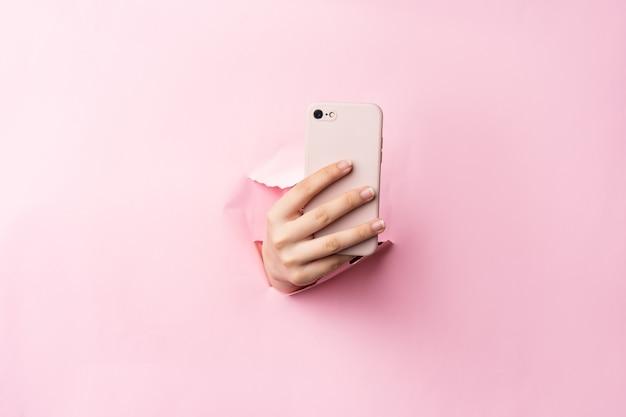 Ramię kobiety trzymającej telefon