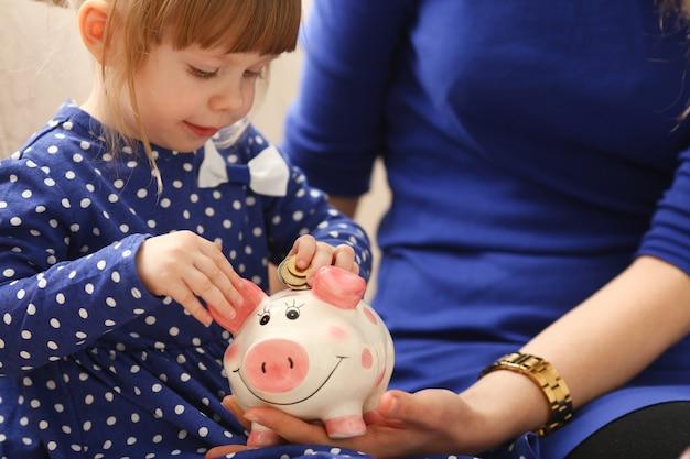 Ramię małej dziewczynki wkłada monety do skarbonki