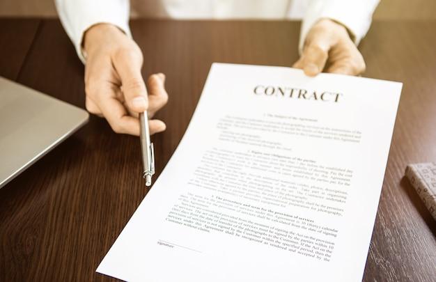 Ramię męskie oferty formularza umowy i srebrne pióro do podpisania zbliżenie. ciepły blask światła słonecznego.