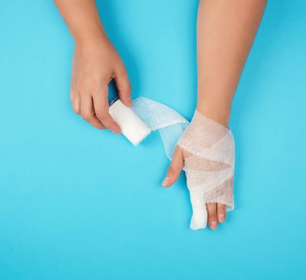 Ramię owinięte w biały sterylny bandaż na niebieskim tle