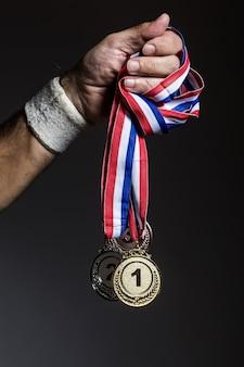 Ramię starszego sportowca posiadającego trzy złote, srebrne i brązowe medale na ciemnym tle. koncepcja sportu i zwycięstwa.
