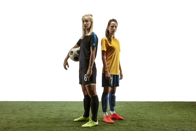 Ramię w ramię. młoda kobieta piłka nożna lub piłkarze w sportowej i buty treningowe na białym tle. pojęcie zdrowego stylu życia, sportu zawodowego, ruchu, ruchu. pewny wygląd.