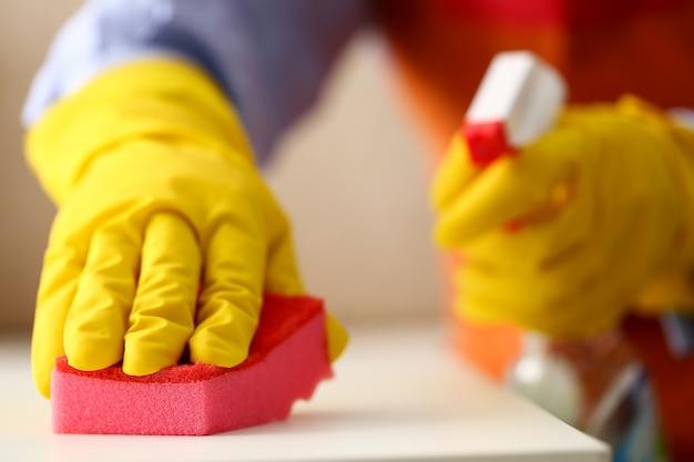 Ramię w żółtej lateksowej rękawicy ochronnej, usuwającej kurz